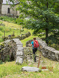Woman hiking in the High Pyrenees on old bridge in village of Heas, France