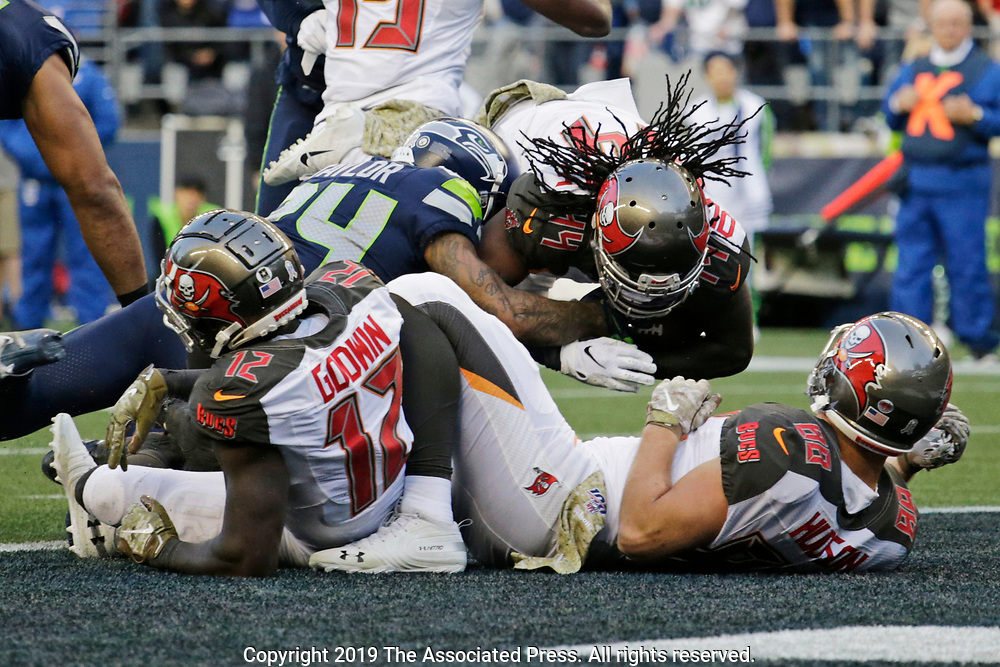 Tampa Bay Buccaneers running back Dare Ogunbowale, upper right, dives for a touchdown against the Seattle Seahawks during the second half of an NFL football game, Sunday, Nov. 3, 2019, in Seattle. (AP Photo/John Froschauer)