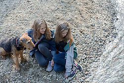 Teenage girls sitting at riverside with their dog, Freiburg im Breisgau, Baden-Wuerttemberg, Germany