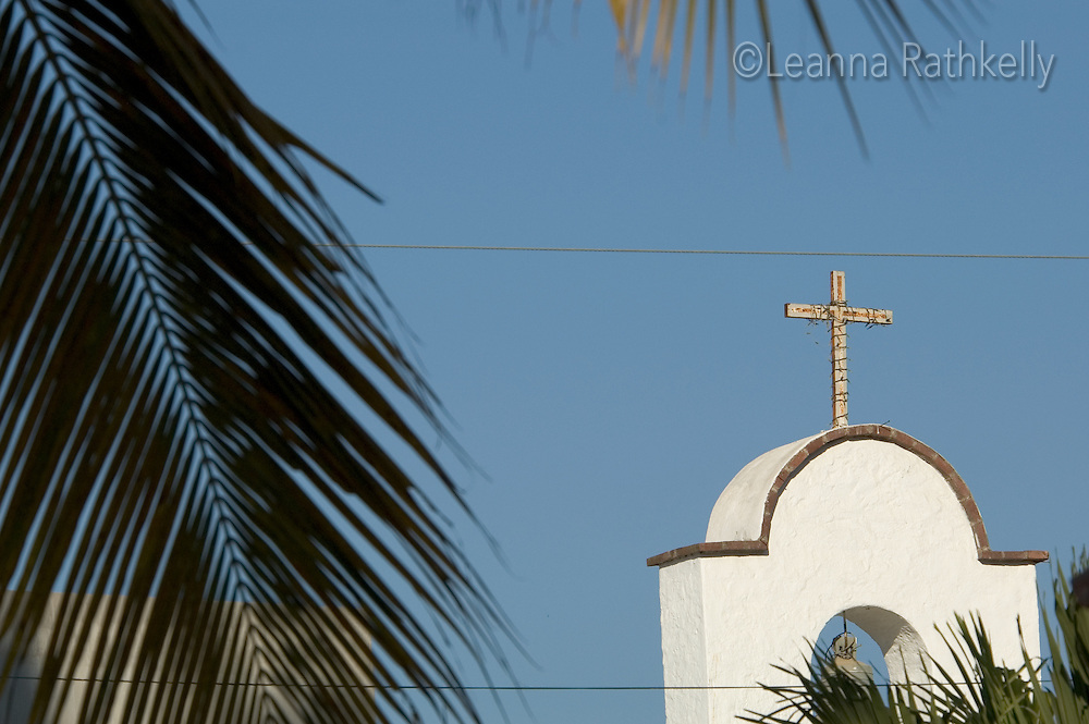 A church displays its cross amongst the palm trees of Sayulita, Mexico