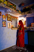 A hindu woman prays at the improvised altar with deities and statues inside the family's, Salawas, Rajasthan, India.