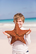 Young boy holds a Red Cushion sea star along the pink sands beach in Dunmore Town, Harbour Island, The Bahamas