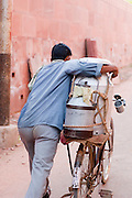 Water seller pushing his bike through the streets of Agra, India
