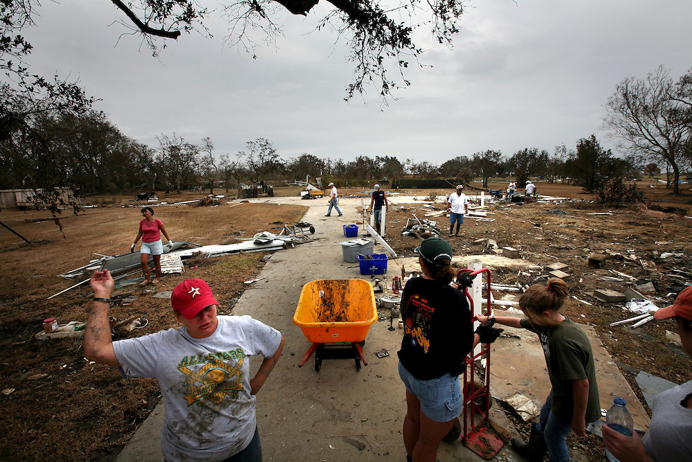ORG XMIT: *S0424385076* (09/19/08) ---  Scottie Berg, front left, talks with family and friends as they collect debris from the site where her brother's house once stood in Sabine Pass Friday September 19, 2008.  Hurricane Ike swept the home off the foundation.