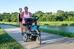 Lady with child in stroller on Trinity Trails near the Trinity River, Fort Worth, Texas, USA.