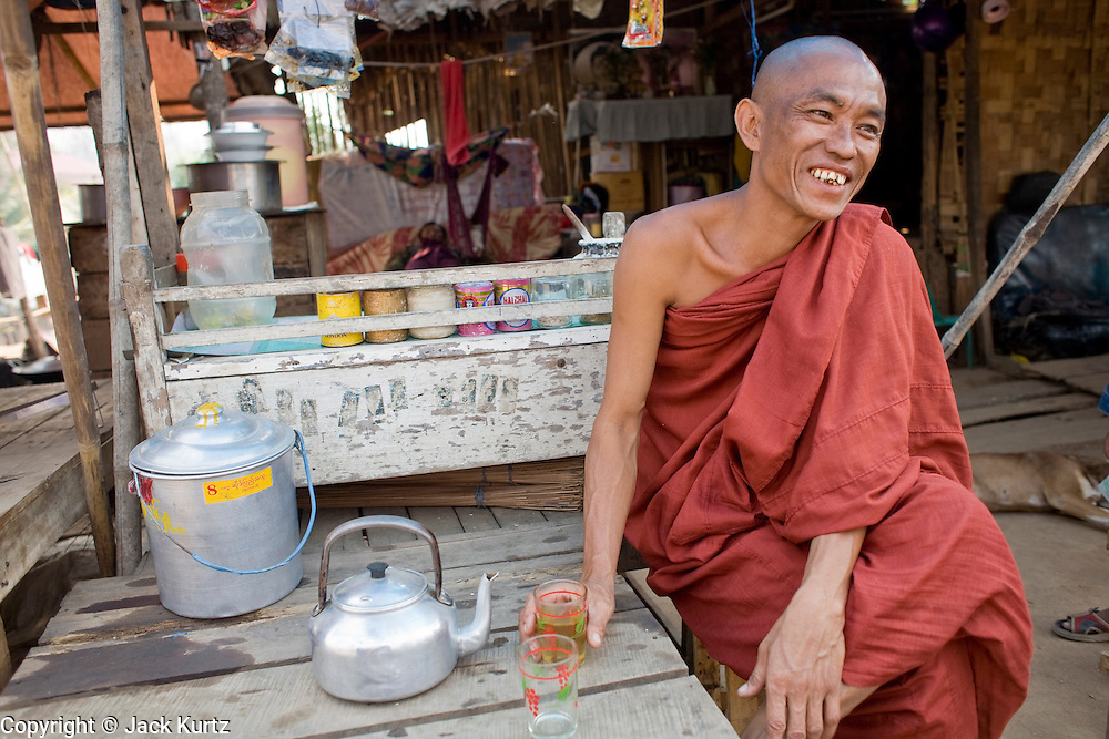 26 FEBRUARY 2008 -- MYAWADDY, MYANMAR: A Buddhist monk drinks tea during his morning rounds for alms in Myawaddy, Myanmar. Myawaddy, a town of about 65,000, is just across the Moei River from Mae Sot, Thailand and is one of Myanmar's leading land ports for goods going to and coming from Thailand. Most of the businesses in the town are geared towards trade, both legal and illegal, with Thailand. Human rights activists from Myanmar maintain that the Burmese government controls the drug smuggling trade between the two countries and that most illegal drugs made in Myanmar are shipped into Thailand from Myawaddy.   Photo by Jack Kurtz