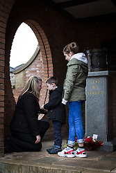 © Licensed to London News Pictures . 29/03/2015 . Manchester , UK . Rebecca Rigby ( Lee Rigby's widow ) (l) and son Jack (c) in front of the memorial . A bronze drum , in memory of Fusilier Lee Rigby , is unveiled in Middleton Memorial Gardens , North Manchester at a memorial service in his honour . Rigby was murdered in a terrorist attack in Woolwich in May 2013 . Photo credit : Joel Goodman/LNP