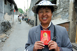 Female hawker selling copies of Chairman Mao`s Little Red Book in a traditional old Beijing hutong