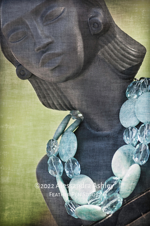 Stone and bead necklace displayed on mannequin at street market.
