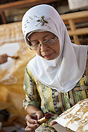 Making batik - Indonesian woman applying wax using a wax pen called canting. Plentong, Yogyakarta, Central Java, Indonesia.
