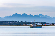 A fishing boat (the Moon Shine) anchored in the Nicomekl River with the Golden Ears (Mount Blandshard) and Mount Robie Reid(right) in the background.  Photographed from Blackie Spit in Surrey, British Columbia, Canada.