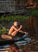 A local man paddling his boat in the floating village of Kompong Phluk on the great Tonlé Sap lake, Cambodia