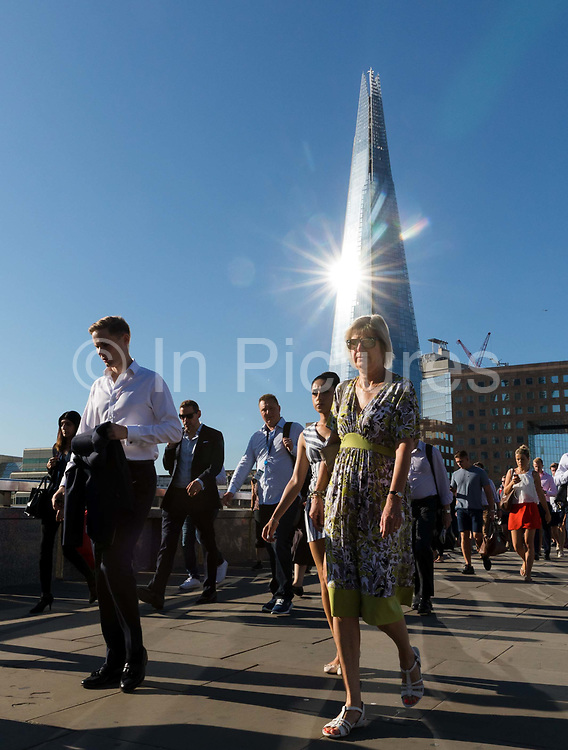 Commuters walk to work across London Bridge as the sun reflects on the London Shard in London, England on August 03, 2018 during hot sunny weather as the heatwave continues in the capital and across Europe.