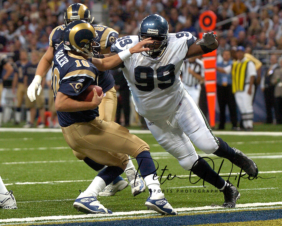 St. Louis Rams quarterback Mark Bulger (10) is pressured by Seattle defensive end Rocky Bernard (99) in the second half at the Edward Jones Dome in St. Louis, Missouri, October 15, 2006.  The Seahawks beat the Rams 30-27.<br />