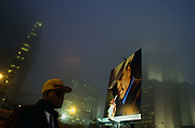 In evening city mist, a car park attendant stands guard over his downtown Atlanta parking lot. Next to him is a giant billboard for Marlboro with the classic face of the Marlboro cowboy, depicted drawing on a cigarette and wearing the traditional wide-brimmed stetson. They are low in the frame and the gloomy and eerie mist sits oppressively around the tall buildings, obscuring their top floors. Office lights still burn and a bright street light shines with the intensity of a small solar flare. The Marlboro Man is part of a tobacco advertising campaign for Marlboro cigarettes. The Marlboro Man was first conceived by the Leo Burnett agency in 1954. The image involves a rugged cowboy or cowboys, in nature with only a cigarette. The ads were originally conceived as a way to popularize filtered cigarettes, which at the time were considered feminine. Actor and author William Thourlby is said to have been the first Marlboro Man. The models who portrayed the Marlboro Man were New York Giants Quarterback Charley Conerly, New York Giants Defensive Back Jim Patton, Darrell Winfield, Dick Hammer, Brad Johnson, Bill Dutra, Dean Myers, Robert Norris, Wayne McLaren, David McLean and Tom Mattox. Two of them, McLaren and McLean, died of lung cancer.