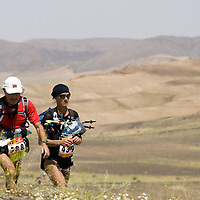 25 March 2007: Runner #588 Fulvio Villano (left) of Italia and #439 Anke Molkenthin of Germany walk across a blooming desert because of a rainy winter between Irhs and Khermou during the first stage of  the 22nd Marathon des Sables, a 6 days and 151 miles endurance race with food self sufficiency across the Sahara Desert in Morocco. Each participant must carry his, or her, own backpack containing food, sleeping gear and other material.