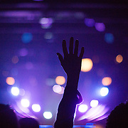 A member of Elevation Church raises her hand in worship during a Saturday night service at the Elevation Matthews campus.