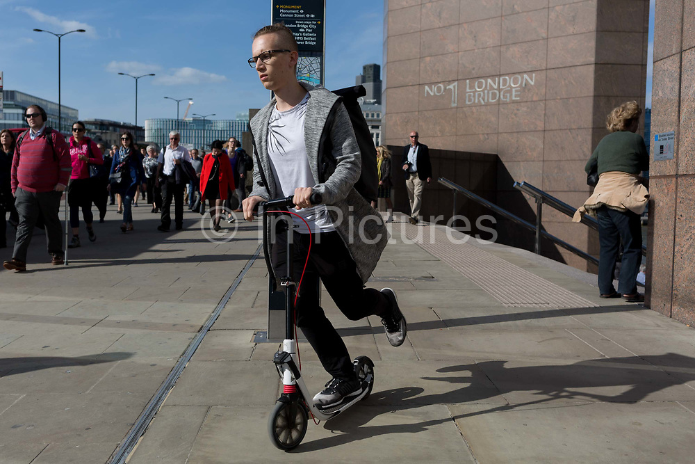 A person scoots and commuters and other pedestrians walk over London Bridge, the oldest of the capitals crossing over the river Thames between the capitals financial district, the City of London, and Southwark on the south bank, on 17th May 2018, in London, UK.
