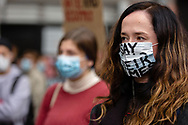 A woman wearing a facemask with Say Their Name written on it stands amongst fellow protesters during a Black Lives Mater rally on 06 June, 2020 in Melbourne, Australia. This event was organised to rally against aboriginal deaths in custody in Australia as well as in unity with protests across the United States following the killing of an unarmed black man George Floyd at the hands of a police officer in Minneapolis, Minnesota. (Photo by Dave Hewison/ Speed Media)