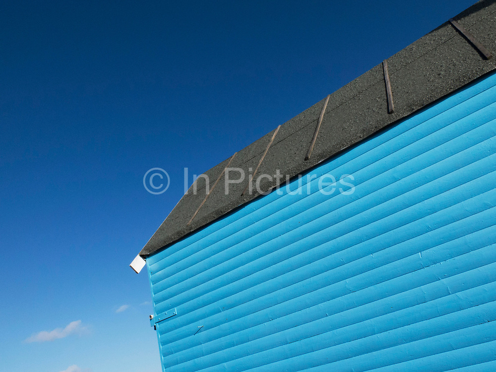 Blue fisherman's hut against a clear blue sky. Whitstable is a seaside town located on the north coast of Kent, in southeast England, UK. Whitstable is famous for its oysters. It's distinctive character is popular with tourists, and its maritime heritage is celebrated with the annual oyster festival. Freshly caught shellfish are available throughout the year at several seafood restaurants and pubs in the town.