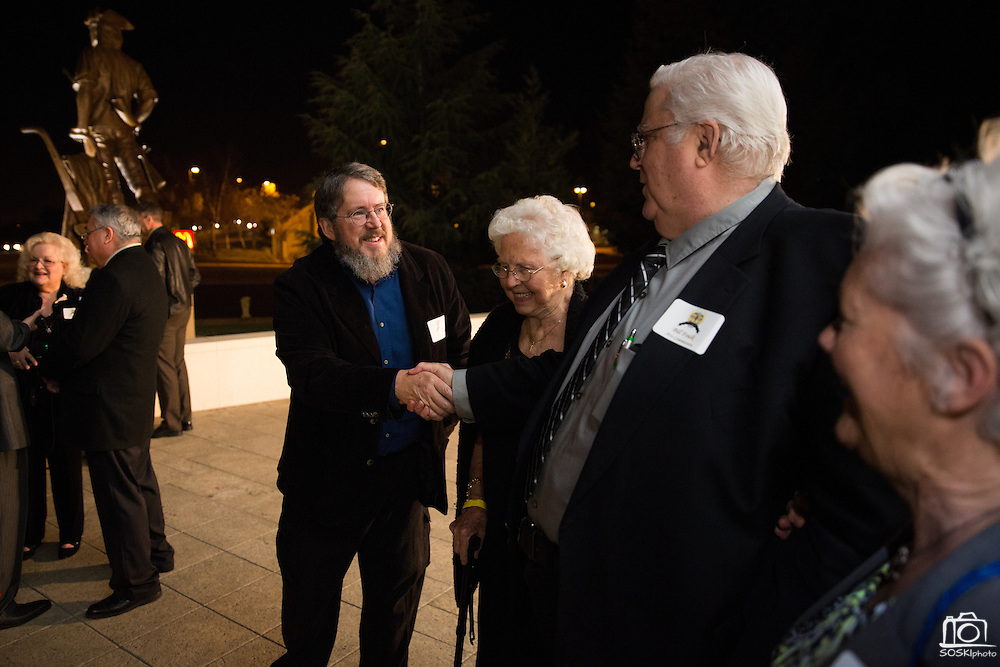 Wyoming sculptor David Alan Clark, center, talks with Bill Foulk, second from right, and family about the Milpitas Minute Man sculpture during the City of Milpitas 60th Anniversary Gala at Milpitas City Hall in Milpitas, California, on January 25, 2014. (Stan Olszewski/SOSKIphoto)