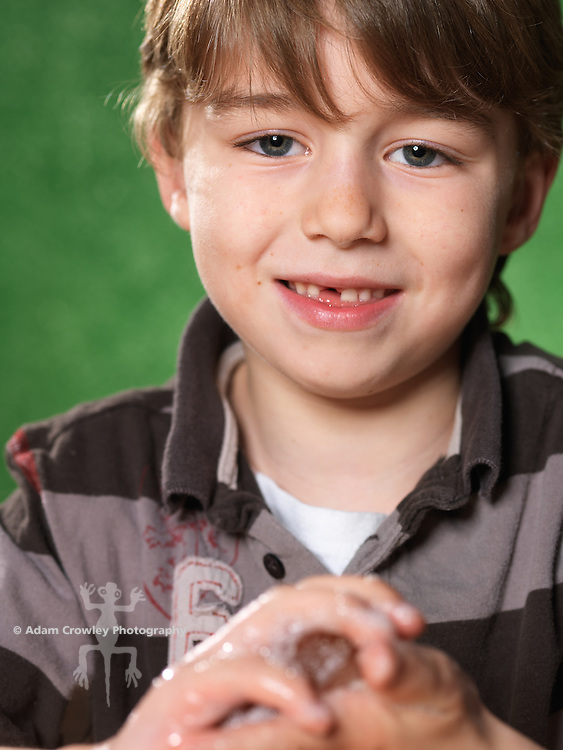 Portrait of boy (7 years old) washing his hands with soap and water.