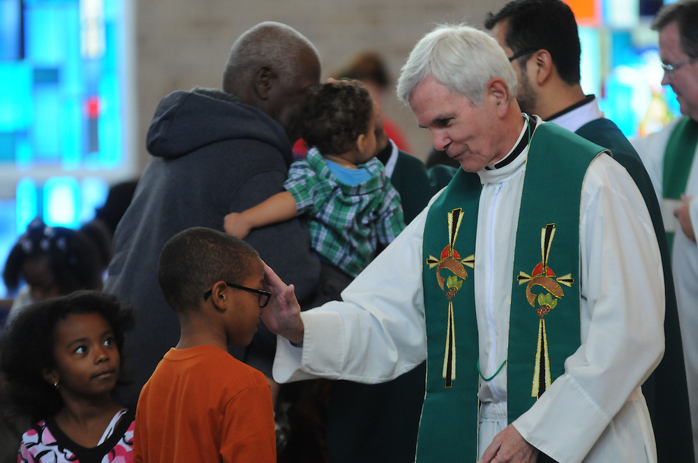 Father John Canary blesses children during a mass at St. Eulalia Catholic Church in Maywood.