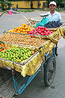 Phnom Penh Street Vendor, peddling fresh fruits from his cart.  One thing that Cambodians are rich in is the wide variety of tropical fruits that are readily available from street vendors such as this guy.