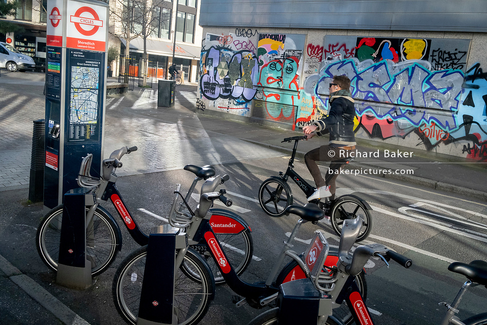 Santander rental bikes await their next riders, in front of a cycling commuter who indicates with an outstretched arm a right turn, in Shoreditch where graffiti covers the exterior of a former office property, on 26th February 2021, in London, England.