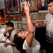 Benito Carriaga watches his wife, Paula Carriaga, react after a healing session as Alberto Salinas channels the spirit of Niño Fidencio and performs a healing with Guadalupe Saavedra inside his sanctuary for the Mexican folk saint in Edinburg. <br /> Nathan Lambrecht/The Monitor