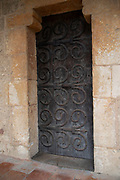 Ornately decorated hinges on a door at Fontfroide Abbey near Narbonne, France. Fontfroide Abbey is a former Cistercian monastery in France, situated 15 kilometers south-west of Narbonne. It was founded in 1093 by Aimery I, Viscount of Narbonne, but remained poor and obscure, and needed to be refounded by Ermengarde, Viscountess of Narbonne. The abbey fought together with Pope Innocent III against the heretical doctrine of the Cathars who lived in the region. It was dissolved in 1791 in the course of the French Revolution. The premises, which are of very great architectural interest, passed into private hands in 1908, when the artists Gustave and Madeleine Fayet dAndoque bought it to protect the fabric of the buildings from an American collector of sculpture. They restored it over a number of years and used it as a centre for artistic projects. It still remains in private hands. Today it is open to paying guests.