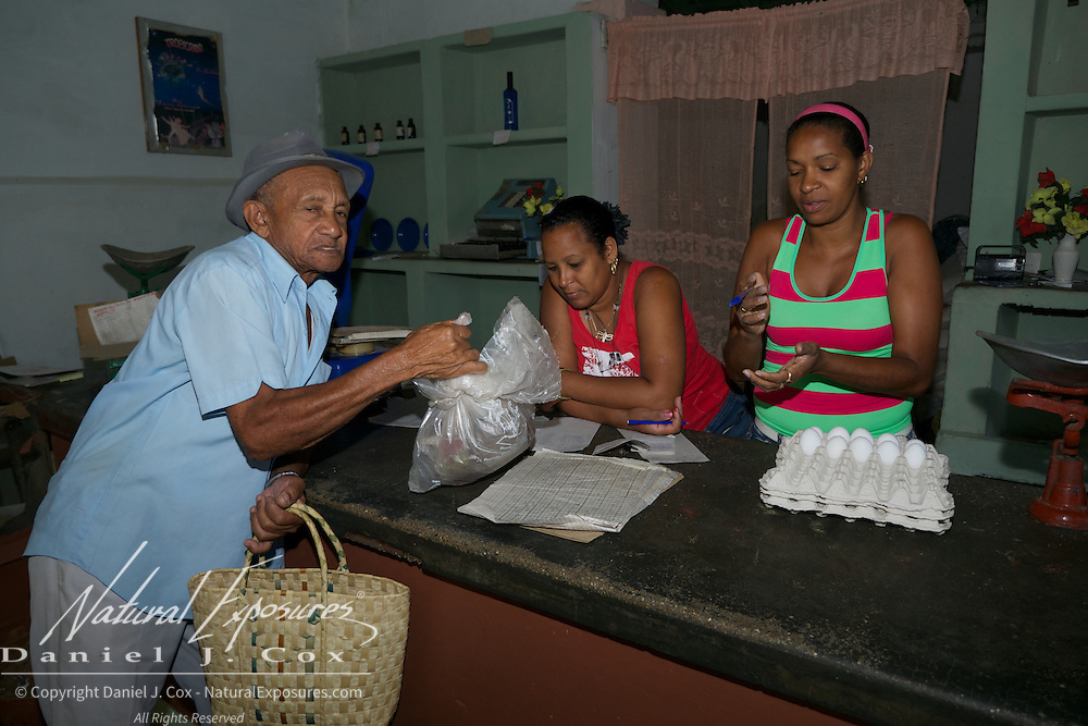 A woman who runs one of the Cuba government's food ration store waits for local residents to come in for some of their monthly food rations.