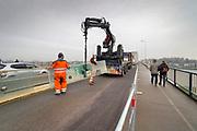 Nederland, Nijmegen, 10-12-2020  Aannemer KWS deed groot onderhoud aan de oude, iconische Waalbrug . De brug werd afgelopen jaar grondig gerenoveerd en opgeknapt. Het bleek dat de oude verf chroom6 bevat waardoor de schildersbeurt is uitgesteld vanwege extra veiligheidsmaatregelen. De brug is gebouwd in 1936 en was toen de langste boogbrug van Europa . Glaszetters brengen een glascherm aan langs het vernieuwde fietspad.Foto: Flip Franssen