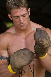 Muscular blond young man putting on boxing gloves