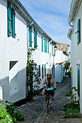 Traditional street scene woman cycles along cobbled alleyway at St Martin de Re,  Ile de Re, France