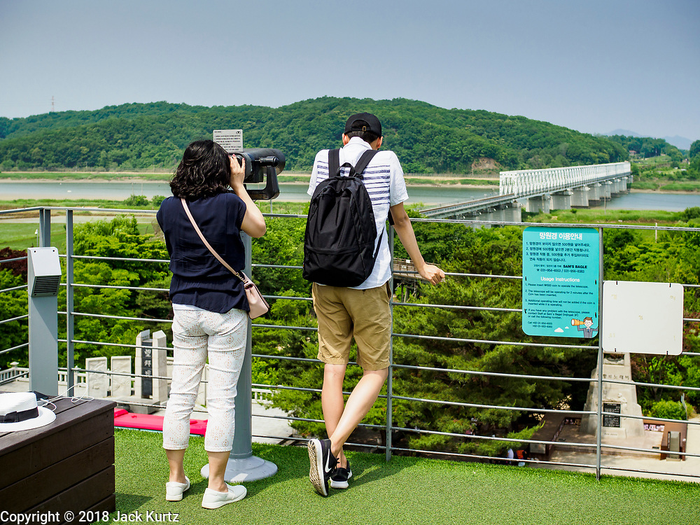 09 JUNE 2018 - IMJINGAK, PAJU, SOUTH KOREA: Tourists look past the Freedom Bridge into North Korea from a lookout on the South Korean side of the Korean DMZ in Imjingak. Imjingak is a park and greenspace in South Korea that is farthest north most people can go without military authorization. The park is on the south bank of Imjin River, which separates South Korea from North Korea and is close the industrial park in Kaesong, North Korea that South and North Korea have jointly operated.     PHOTO BY JACK KURTZ