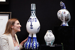 © licensed to London News Pictures. LONDON, UK  08/06/2011. Elvira Pilatti examines vases, valued at up to £100,000, made by Picasso at the Olympia International Fine Art & Antiques Fair. In total 30,000 items are on sale from 150 dealers and each is vetted for authenticity by a panel of experts. The show opens in Olympia tomorrow (Thursday) and runs for 11 days. Please see special instructions for usage rates. Photo credit should read CLIFF HIDE/LNP
