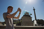 With a confusing perspective and scale, a spectator photographs artist Yinka Shonibare's artwork called Nelson's Ship in a Bottle on the Fourth Plinth in London's in Trafalgar Square. The artwork features a 1:29 scale replica of Lord Nelson's original HMS Victory commemorating the Battle of Trafalgar in 1805, Shonibare said his version with its textile sails with African and batik prints reflects the multicultural and diverse capital. The 2.35m high ship inside a specially-made glass bottle, will be in place for 18 months. 37 large sails are made of patterns which are commonly associated with African dress and culture. The patterns also look back at the path of colonialism as the patterns were inspired by Indonesian batik design, which were mass produced by the Dutch and sold to the colonies in West Africa. The Fourth Plinth is in the north-west of the Square.