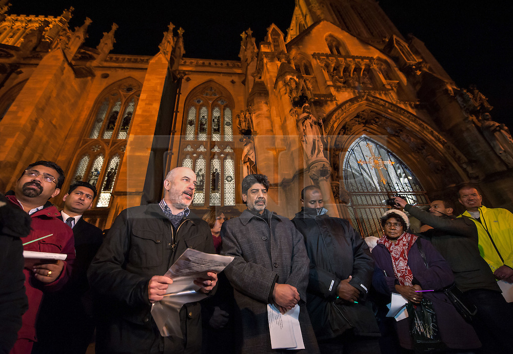 """© Licensed to London News Pictures. 17/11/2015. Bristol, UK.  Vigil for the victims of the Paris terrorist attacks at Bristol Cathedral.  Religious and community leaders including Peter Brill from Salaam Shalom (speaking at left) and Arif Khan (centre) chair of the Council of Mosques. The Muslim community in Bristol organised a candle-lit vigil for all faiths and backgrounds at Bristol Cathedral to show solidarity with the victims of the Paris attacks which are claimed by IS (Islamic State).  The management and Imaam's of Bristol's Easton Jamia Masjid, Bristol's biggest mosque, released a statement saying they have been shocked and saddened by the attacks on innocent people in France. """"We strongly condemn the terrorist atrocities in France, these sickening crimes are an attack against all of humanity.  As a local Muslim place of worship we send our condolences from our local community and congregation to the people of France.  During this very dark hour they will see compassion and solidarity from around the world"""".  Photo credit : Simon Chapman/LNP"""