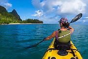 Woman sea kayaking on the Na Pali Coast, Island of Kauai, Hawaii USA