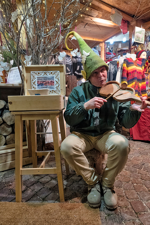 """BUDAPEST, HUNGARY - DECEMBER 07:  A stall holder plays some music at the """"Basilica"""" Christmas fair on December 7, 2017 in Budapest, Hungary. The traditional Christmas market and lights will stay until 31st December 2017."""