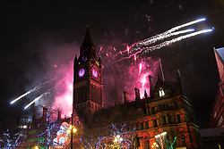 © Licensed to London News Pictures . 31/12/2018. Manchester, UK. Thousands watch as Manchester celebrates the start of 2018 , with a fireworks display in front of the Town Hall in Albert Square . This year's celebration sees additional security, including concrete barriers around the square and bag searches and the event includes a poetry reading by Tony Walsh , in memory of those who were killed at a terrorist attack after at the Manchester Arena in May 2017. Photo credit: Joel Goodman/LNP