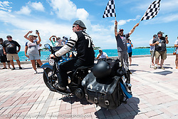 Gary Shorman riding his 1940 Harley-Davidson WL750cc Flathead over the finish line of the Cross Country Chase motorcycle endurance run from Sault Sainte Marie, MI to Key West, FL. (for vintage bikes from 1930-1948). The Grand Finish in Key West's Mallory Square after the 110 mile Stage-10 ride from Miami to Key West, FL and after covering 2,368 miles of the Cross Country Chase. Sunday, September 15, 2019. Photography ©2019 Michael Lichter.
