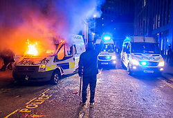 """© Licensed to London News Pictures;21/03/2021; Bristol, UK. Protestors walk by a police van which has been set on fire as police clash with protesters outside New Bridewell Police Station on Sunday evening during a """"Kill the Bill"""" protest against Police, Crime, Sentencing and Courts Bill takes place through the centre of Bristol during the Covid-19 coronavirus pandemic in England. The Bill proposes new restrictions on protests. Lockdown restrictions have been partly lifted to allow people to gather outdoors socially in households, bubbles, or to meet one person from another household, but the police say protests are not allowed under the current Covid regulations. Photo credit: Simon Chapman/LNP."""