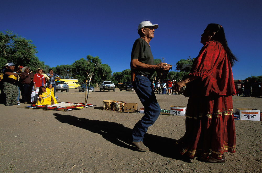 Apache Indians dance at a Sunrise Dance, the first menstruation ceremony of an Apache girl, ton the San Carlos Apache Indian Reservation in Arizona, USA. The girls herself dances in a kneeling position. During the ceremony the girl 'becomes' Changing Woman, the mythical founder of the Apache Tribe, and this part of the ceremony is an enactment of when Changing Woman was impregnated by the sun and gave birth to a son. Behind the girl stands her godmother and behind her the medicine man  and his assistants sing and beat their drums. The long row of cartons filled with snacks and drinks in front of the girl symbolises a life without material wants. The rites are supposed to prepare the girl for adulthood and to give her a long and healthy life.