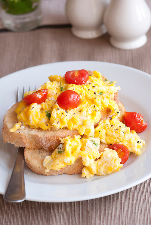 Toast with scrambled eggs, cherry tomatoes and chives