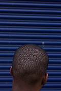 A detail of an anonymous young man's head on a backstreet in Hackney. Blue shutters similar to those on many small businesses are in the background and their horizontal stripes contrast with the youth's hair, which we see from the rear to ensure his anonymity. His head is closely cropped and we see his ears and dark skin from either mixed-race ethnicity of North African.