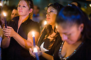11 OCTOBER 2010 - PHOENIX, AZ:  LIZ MONTALVO (center) and others participate in a candle light vigil in front of Phoenix police headquarters Monday night. About 300 people gathered at the Phoenix Police Department headquarters building Monday night to protest the shooting of Daniel Rodriguez and his dog. The officers responded to a 911 call made by Rodriguez' mother. A scuffle ensued when they arrived and Phoenix police officer Richard Chrisman shot Rodriguez, who was unarmed, and his dog. Chrisman then allegedly filed a false report about the event. He has been arrested on felony assault charges. The event has angered some in the Latino community and they have held a series of protests at the police headquarters. They want Chrisman charged with murder.    Photo by Jack Kurtz