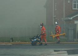 © Licensed to London News Pictures. 01/09/2013. Leyland, UK Emergency workers move a generator. The scene at Leyland St Mary's Catholic Technology College in Leyland, Lancashire as it was devastated by the blaze at 4pm yesterday (1st September 2013), which saw 100ft flames - and was tackled by 125 firefighters and 20 engines. Photo credit : Pat Tack/LNP