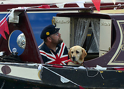© Licensed to London News Pictures. 06/05/2013. London, UK A man and his dog watch the boat handling competition from their boat.  A Colourful gathering of canal boats in the hot bank holiday sunshine today in West London 6th May 2013. Organised by volunteers from Inland Waterways Association (IWA), The Canalway Cavalcade, which has taken place in Little Venice every year since 1983, sees around 130 boats moored along a stretch of the Grand Union Canal in London. Photo credit : Stephen Simpson/LNP